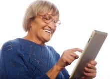Mujer feliz mayor que usa el ipad Imagen de archivo libre de regalías