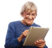 Mujer feliz mayor que usa el ipad imágenes de archivo libres de regalías
