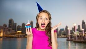 Mujer feliz o muchacha adolescente con la magdalena del cumpleaños Imagenes de archivo