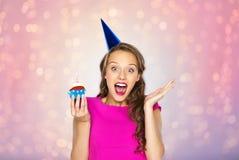 Mujer feliz o muchacha adolescente con la magdalena del cumpleaños Fotografía de archivo libre de regalías