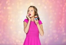Mujer feliz o muchacha adolescente que come la magdalena del cumpleaños Fotos de archivo