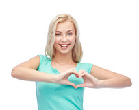 Mujer feliz o muchacha adolescente que muestra suspiro de la forma del corazón Imagen de archivo