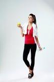 Mujer feliz pensativa joven del deporte con la manzana y botella de agua Foto de archivo libre de regalías