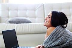 Mujer feliz pensativa que miente en el piso con el ordenador portátil Foto de archivo