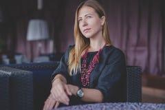 Mujer feliz pensativa que recuerda mirando el lado que se sienta en una terraza de la barra Fotos de archivo