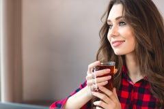 Mujer feliz pensativa que se sostiene de cristal con té Imágenes de archivo libres de regalías