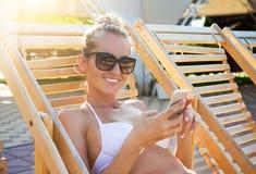 Mujer feliz por la piscina con un teléfono móvil Imagen de archivo libre de regalías