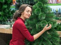 Mujer feliz que abraza un árbol de navidad Celebraciones del día de fiesta del ` s del Año Nuevo Fotos de archivo