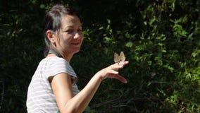 Mujer feliz que admira la mariposa almacen de video