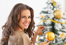 Mujer feliz que adorna el árbol de navidad con la bola de la Navidad Imagen de archivo libre de regalías