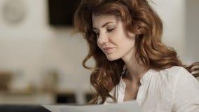 Mujer feliz que analiza datos sobre el sofá Señora sonriente que trabaja en casa almacen de metraje de vídeo