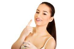 Mujer feliz que aplica la crema hidratante poner crema Imágenes de archivo libres de regalías
