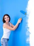 Mujer feliz que aplica la pared con brocha Imagen de archivo libre de regalías