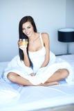 Mujer feliz que bebe el zumo de naranja en cama Fotografía de archivo