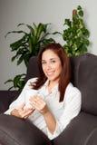 Mujer feliz que bebe té caliente en casa Imágenes de archivo libres de regalías