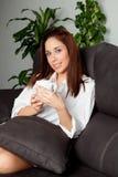 Mujer feliz que bebe té caliente en casa Foto de archivo libre de regalías