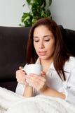 Mujer feliz que bebe té caliente en casa Imagenes de archivo