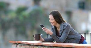 Mujer feliz que bebe y que usa el teléfono en un balcón almacen de metraje de vídeo