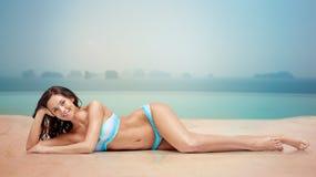 Mujer feliz que broncea en bikini sobre piscina Imagen de archivo