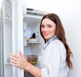 Mujer feliz que busca algo en el refrigerador Foto de archivo