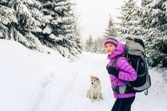 Mujer feliz que camina en bosque del invierno con el perro fotografía de archivo libre de regalías