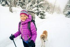 Mujer feliz que camina en bosque del invierno con el perro imágenes de archivo libres de regalías