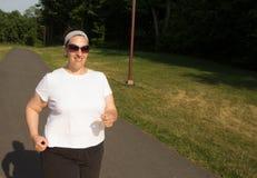 Mujer feliz que camina en una trayectoria en un parque Foto de archivo