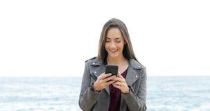 Mujer feliz que camina usando el teléfono en la playa
