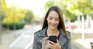 Mujer feliz que camina y que hojea en el teléfono en un parque