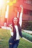 Mujer feliz que canta y que baila en puesta del sol imagen de archivo
