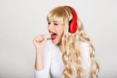 Mujer feliz que canta y que escucha la música Fotografía de archivo