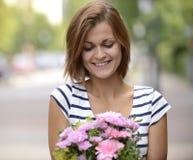 Mujer feliz que celebra el arreglo floral Fotos de archivo