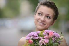 Mujer feliz que celebra el arreglo floral Imagen de archivo
