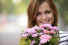 Mujer feliz que celebra el arreglo floral Imagenes de archivo