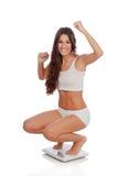 Mujer feliz que celebra su nuevo peso en una escala Imagen de archivo