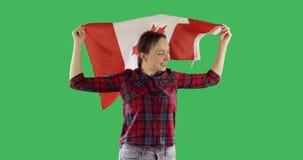 Mujer feliz que celebra una bandera y un funcionamiento canadienses en la pantalla verde dominante de la croma metrajes