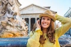 Mujer feliz que charla en el teléfono móvil en la fuente del panteón Fotos de archivo