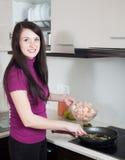 Mujer feliz que cocina camarones en sartén Fotografía de archivo libre de regalías