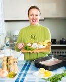 Mujer feliz que cocina pescados Imagen de archivo libre de regalías