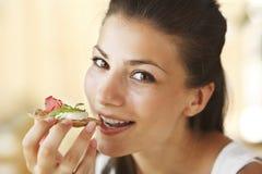 Mujer feliz que come el bocadillo Imágenes de archivo libres de regalías
