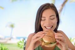 Mujer feliz que come el bocadillo de la hamburguesa en la playa Imágenes de archivo libres de regalías