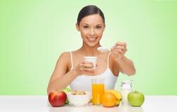 Mujer feliz que come el yogur para el desayuno Fotos de archivo