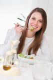 Mujer feliz que come la ensalada Fotos de archivo