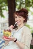 Mujer feliz que come la ensalada de fruta fresca Imagen de archivo libre de regalías