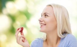 Mujer feliz que come la fresa Foto de archivo