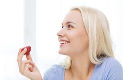 Mujer feliz que come la fresa en casa Imagen de archivo libre de regalías