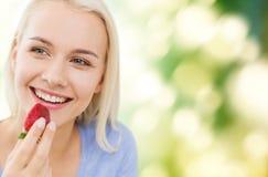 Mujer feliz que come la fresa en casa Imágenes de archivo libres de regalías