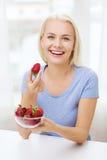Mujer feliz que come la fresa en casa Fotos de archivo
