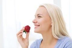 Mujer feliz que come la fresa en casa Fotos de archivo libres de regalías