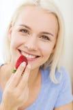 Mujer feliz que come la fresa en casa Imagenes de archivo